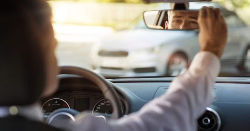 man looking at rearview mirror